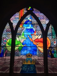 The balcony inside the castle displays beautiful stained glass art.
